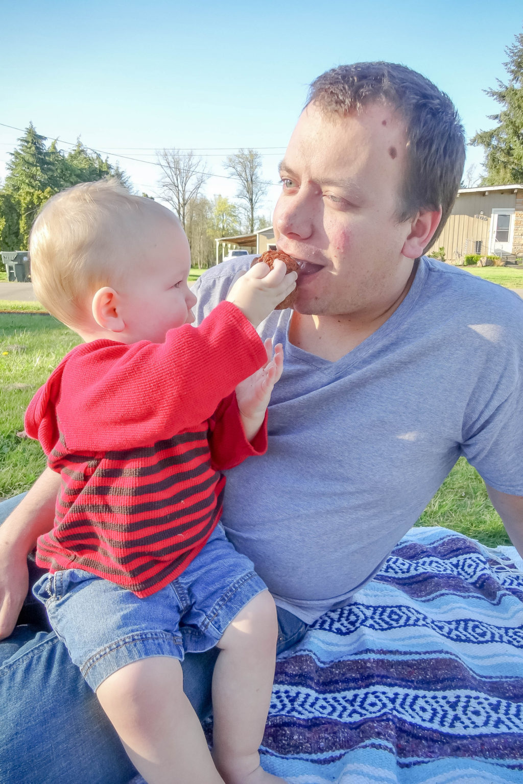 Toddler boy feeding dad a muffin outdoors on a picnic blanket