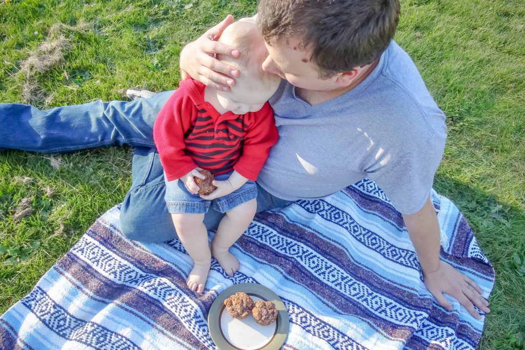 Toddler boy sitting on dad's lap on a picnic blanket.  Dad kissing toddler on head while toddler is holding a muffin with a plate of muffins in front of them