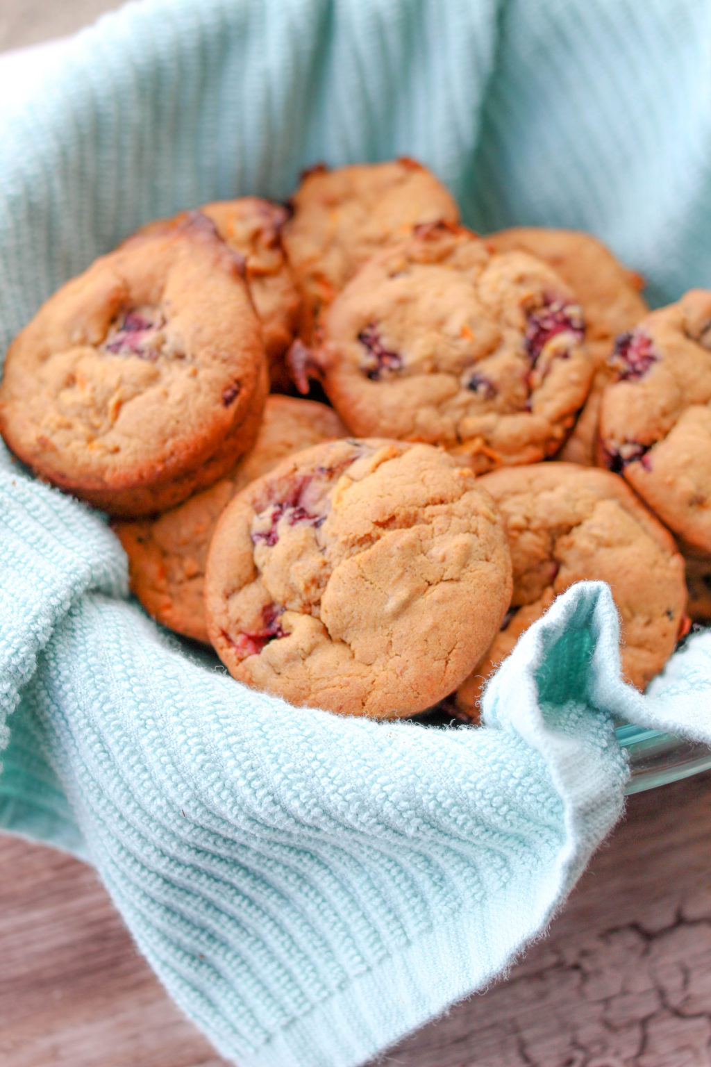 Whole wheat blackberry carrot applesauce muffins piled in a bowl lined with a teal kitchen towel