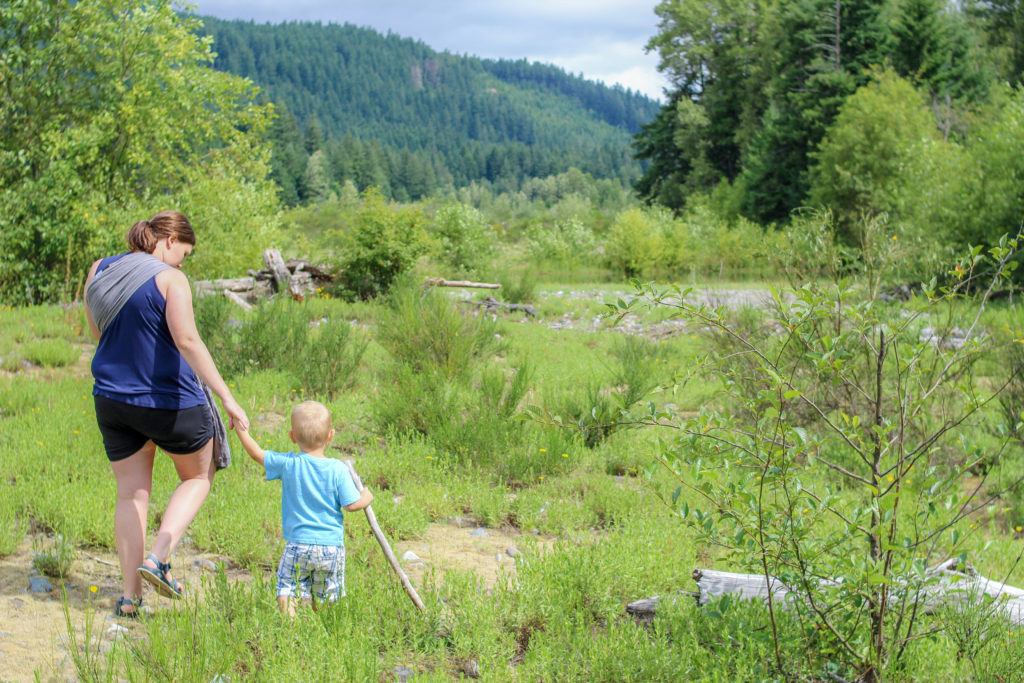 Toddler boy holding mom's hand from behind in nature.