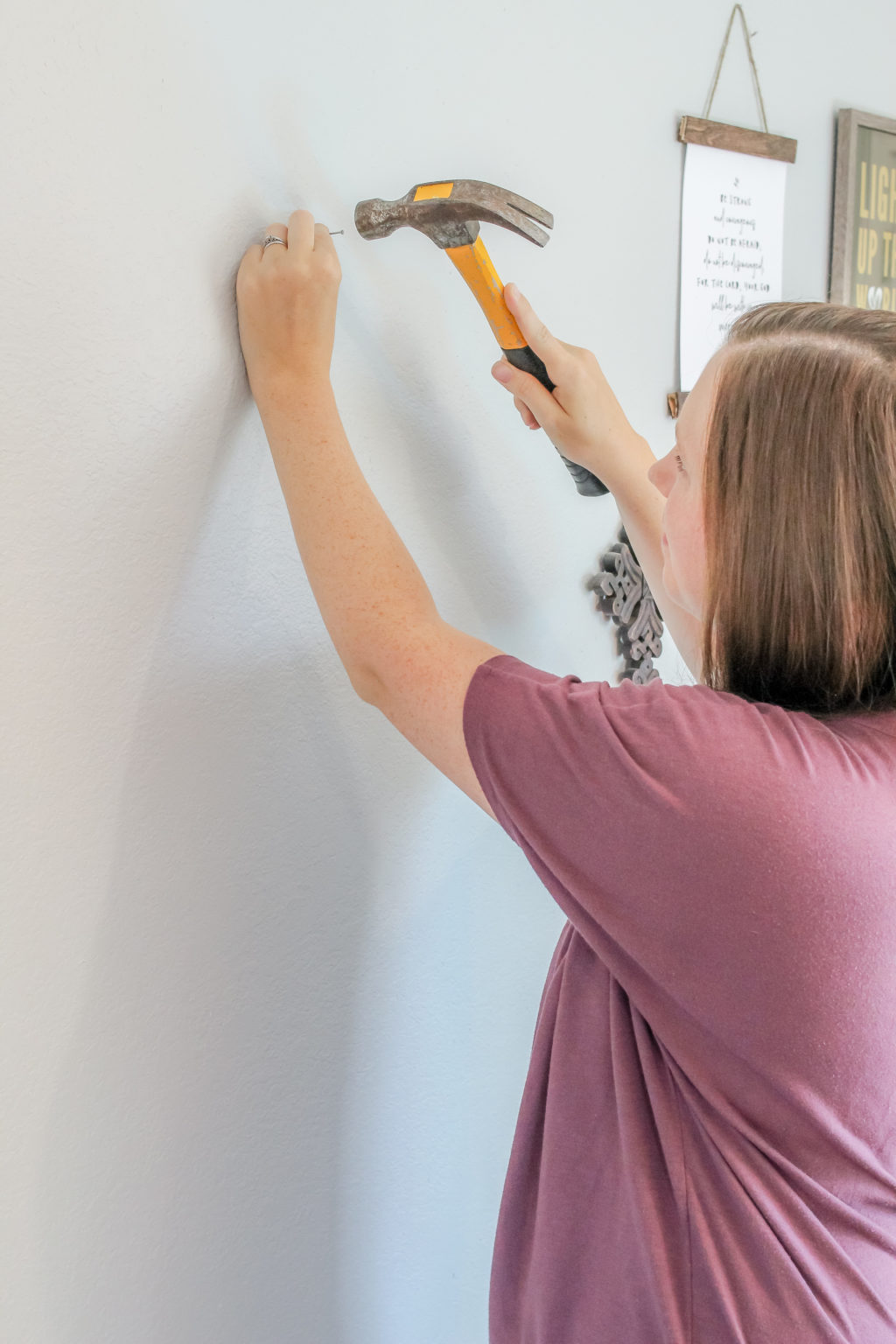 Woman hammering nail into wall