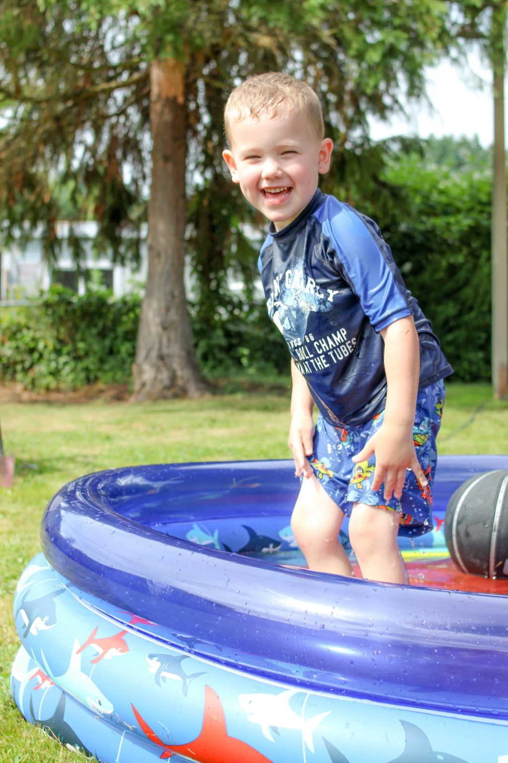 Blond preschool boy standing in wading pool with a huge grin