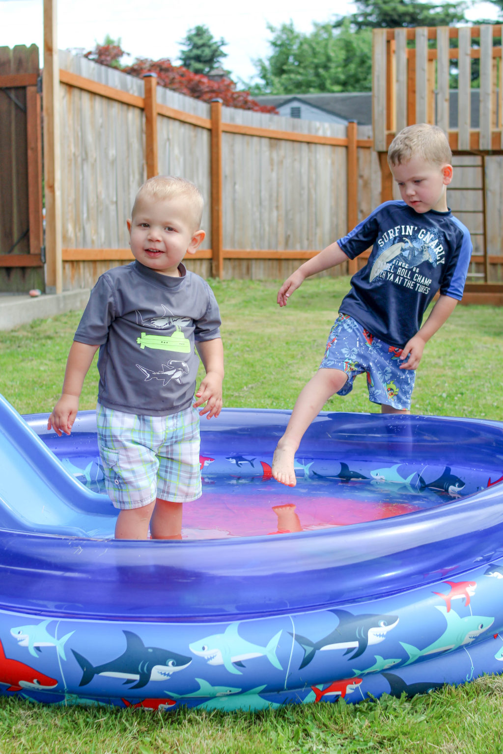 Toddler boy standing in wading pool while preschool boy steps into it