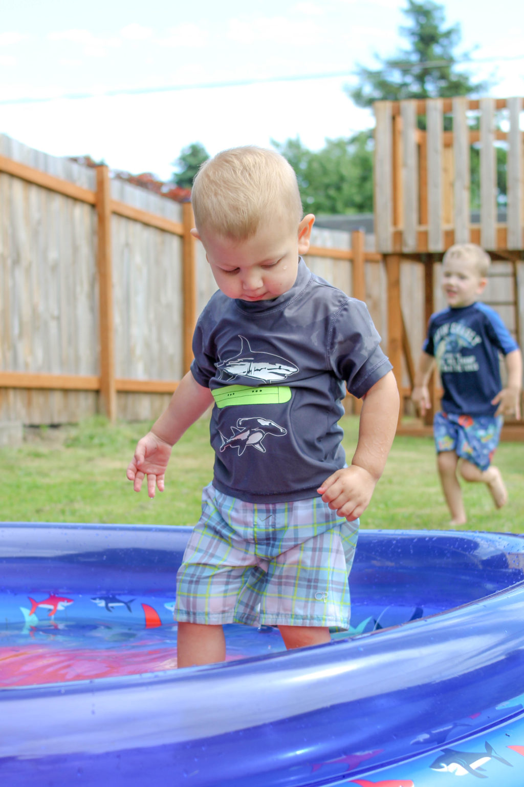 Toddler boy standing in wading pool while preschool boy runs toward him