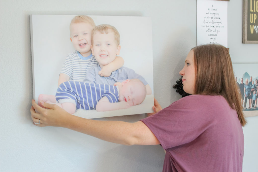 Woman hanging canvas photo of two young boys and baby boy on wall